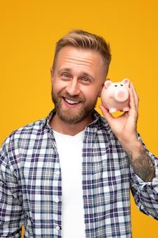 Erfreuter bärtiger mann im karierten hemd, der für kamera lächelt und sparschwein schüttelt