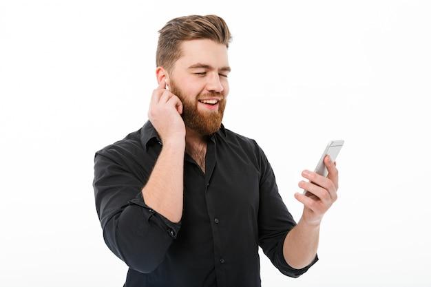 Erfreuter bärtiger mann in hörender musik des hemdes durch smartphone