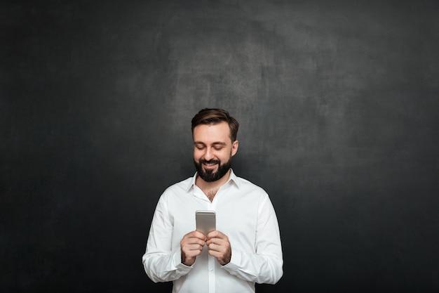 Erfreuter büroangestellter in der schreibentextnachricht des weißen hemdes oder in der blätternzufuhr im sozialen netz unter verwendung des handys über graphit