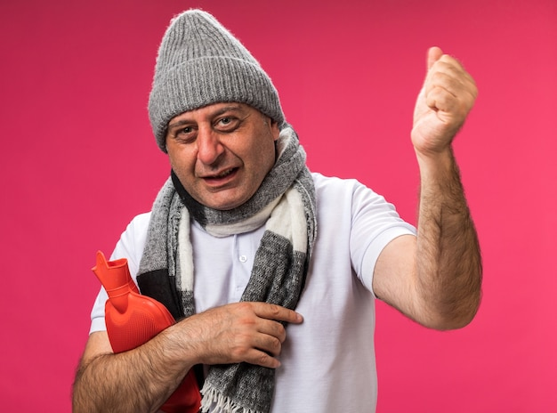 Erfreuter erwachsener kranker kaukasischer mann mit schal um hals, der wintermütze hält, die wärmflasche hält und faust oben auf rosa wand mit kopienraum isoliert hält