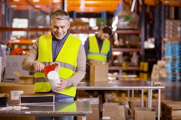 Erfreuter erwachsener mann, der aufkleber auf die flasche setzt, während er im lager arbeitet
