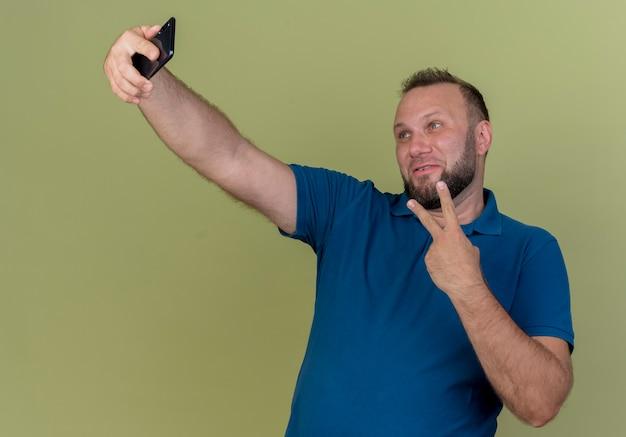 Erfreuter erwachsener slawischer mann, der friedenszeichen tut und selfie nimmt