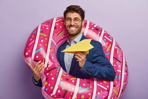 Erfreuter fröhlicher männlicher regisseur kehrt nach den sommerferien zur arbeit zurück, wirft papierflugzeug, steht im aufgeblasenen schwimmring, lächelt positiv