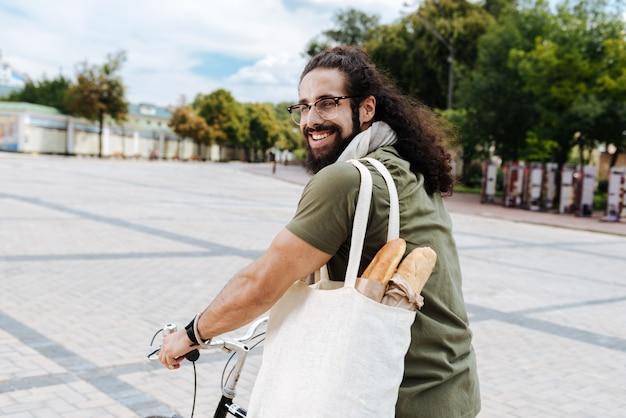 Erfreuter fröhlicher mann, der zu ihnen lächelt, während sie vom supermarkt nach hause gehen