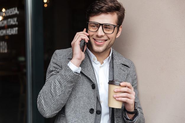Erfreuter geschäftsmann in den brillen und in mantel sprechend durch smartphone
