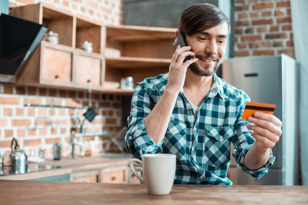 Erfreuter glücklicher netter mann, der eine kreditkarte hält und sie beim bezahlen betrachtet