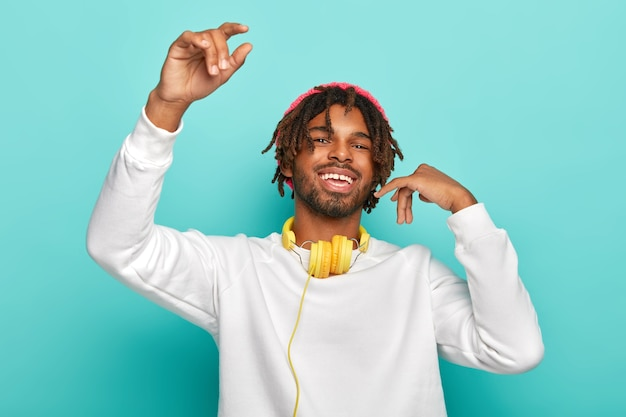 Erfreuter glücklicher teenager mit dreadlocks, hebt die arme, fühlt freude, hört lieblingsmusik über kopfhörer, bewegt sich im rhythmus des liedes, trägt einen weißen pullover