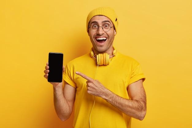 Erfreuter gutaussehender mann zeigt auf den bildschirm des smartphones, lächelt freudig, trägt eine optische brille, einen hut und ein t-shirt
