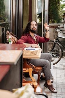 Erfreuter hübscher mann, der auf einen kellner wartet, während er eine bestellung aufgeben möchte