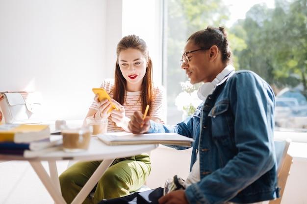 Erfreuter internationaler student, der ein lächeln auf seinem gesicht behält, während er seinem freund zuhört