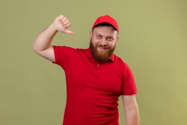 Erfreuter junger bärtiger lieferbote in roter uniform und mütze, die auf sich selbst lächelnd zeigen