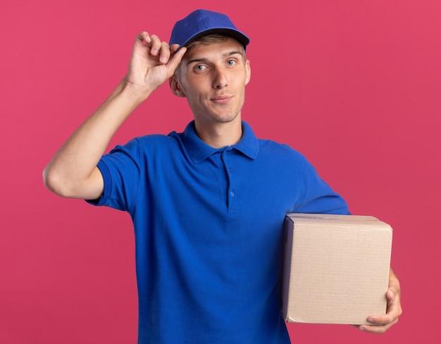 Erfreuter junger blonder lieferjunge setzt hand auf mütze und hält karton auf rosa