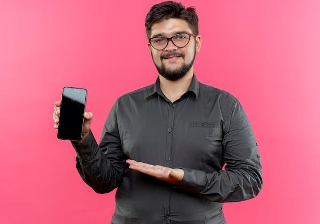 Erfreuter junger geschäftsmann, der brillen hält und mit der hand am telefon zeigt