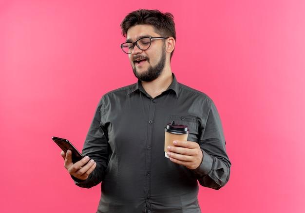 Erfreuter junger geschäftsmann, der eine brille trägt, die tasse kaffee hält und telefon in seiner hand betrachtet