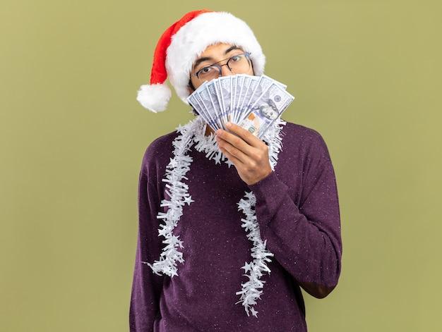 Erfreuter junger gutaussehender kerl mit weihnachtsmütze mit girlande am hals bedecktes gesicht mit bargeld isoliert auf olivgrüner wand