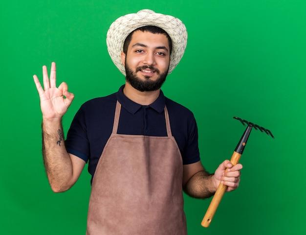 Erfreuter junger kaukasischer männlicher gärtner, der gartenhut hält, der rechen hält und ok zeichen lokalisiert auf grüner wand mit kopienraum gestikuliert