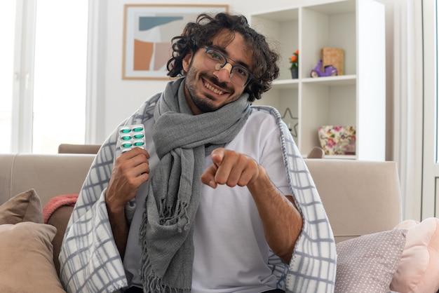 Erfreuter junger kranker kaukasier in optischer brille, eingewickelt in plaid mit schal um den hals, der eine medizinblisterpackung hält und auf die kamera zeigt, die auf der couch im wohnzimmer sitzt