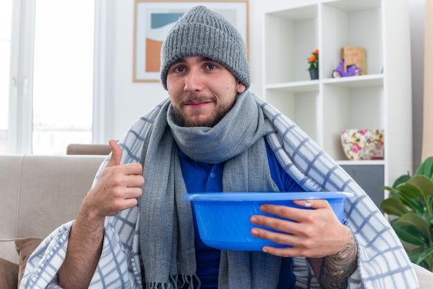 Erfreuter junger kranker mann mit schal und wintermütze, der auf dem sofa im wohnzimmer sitzt und in eine decke gehüllt ist, die wanne hält und nach vorne schaut