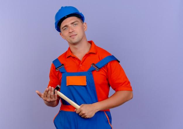 Erfreuter junger männlicher baumeister, der uniform und schutzhelm hält hammer hält