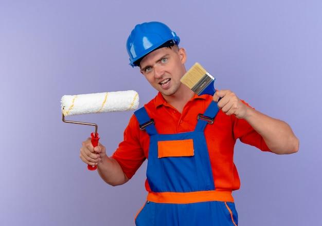 Erfreuter junger männlicher baumeister, der uniform und schutzhelm trägt, der farbroller und pinsel hält