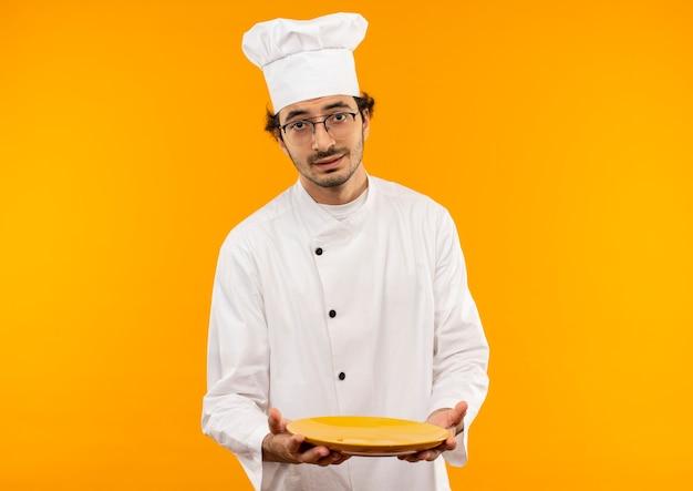 Erfreuter junger männlicher koch, der kochuniform und brille hält platte trägt