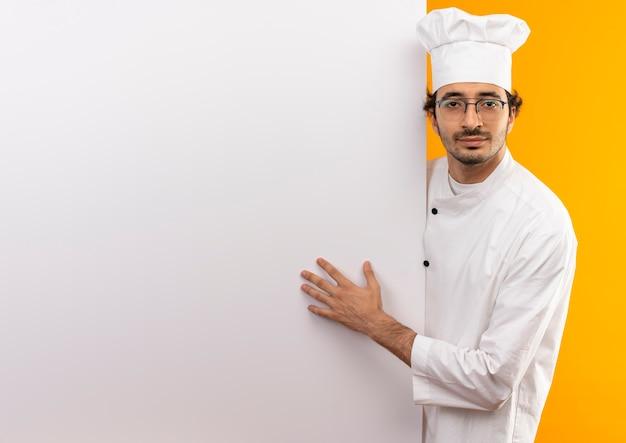 Erfreuter junger männlicher koch, der kochuniform und gläser trägt, die weiße wand halten