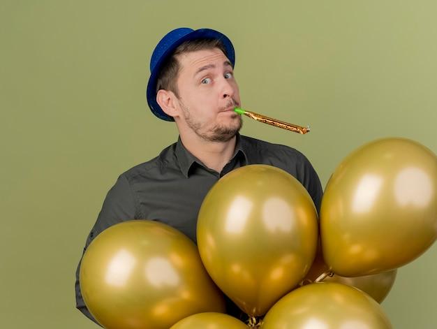 Erfreuter junger party-typ, der schwarzes hemd und blauen hut trägt, der unter luftballons steht, die pfeife lokalisiert auf olivgrün blasen