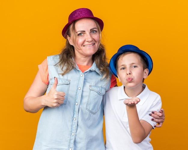 Erfreuter junger slawischer junge mit blauem partyhut, der einen kuss mit der hand sendet, der mit seiner mutter steht, die einen lila partyhut trägt und isoliert auf einer orangefarbenen wand mit kopienraum nach oben greift