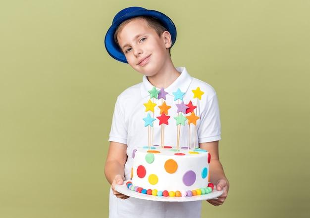 Erfreuter junger slawischer junge mit blauem partyhut, der geburtstagskuchen isoliert auf olivgrüner wand mit kopienraum hält