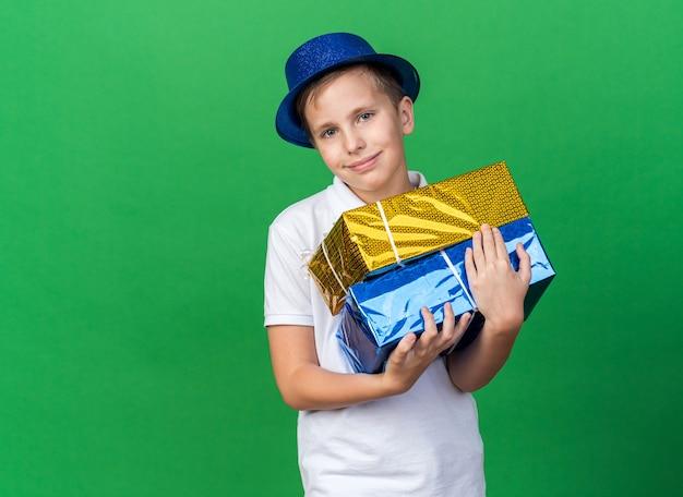 Erfreuter junger slawischer junge mit blauem partyhut, der geschenkboxen hält und isoliert auf grüner wand mit kopienraum schaut