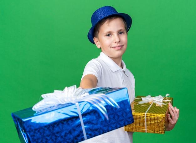 Erfreuter junger slawischer junge mit blauem partyhut, der geschenkboxen isoliert auf grüner wand mit kopienraum hält