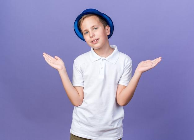 Erfreuter junger slawischer junge mit blauem partyhut, der hände offen hält, lokalisiert auf lila wand mit kopienraum