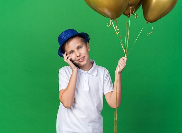 Erfreuter junger slawischer junge mit blauem partyhut, der heliumballons hält und am telefon lokalisiert auf grüner wand mit kopienraum spricht
