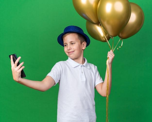 Erfreuter junger slawischer junge mit blauem partyhut, der heliumballons hält und selfie am telefon einzeln auf grüner wand mit kopienraum nimmt