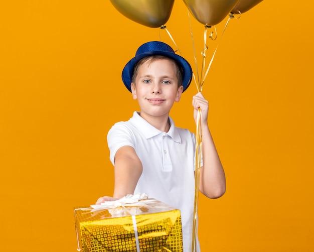 Erfreuter junger slawischer junge mit blauem partyhut, der heliumballons und geschenkbox lokalisiert auf orange wand mit kopienraum hält