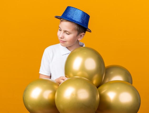 Erfreuter junger slawischer junge mit blauem partyhut, der mit heliumballons steht, die auf orange wand mit kopienraum isoliert werden
