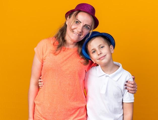 Erfreuter junger slawischer junge mit blauem partyhut, der mit seiner mutter steht, die lila partyhut trägt, lokalisiert auf orange wand mit kopienraum