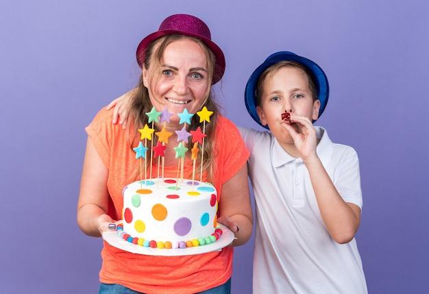 Erfreuter junger slawischer junge mit blauem partyhut, der partypfeife bläst, während seine mutter einen violetten partyhut trägt, der geburtstagskuchen isoliert auf lila wand mit kopienraum hält