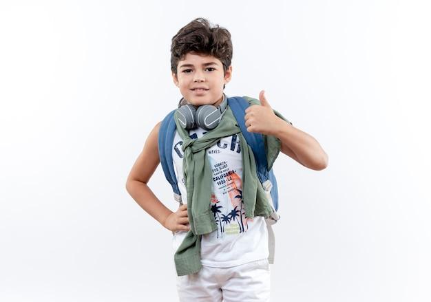 Erfreuter kleiner schuljunge, der rückentasche und kopfhörer trägt und hand auf hüfte seinen daumen nach oben legt