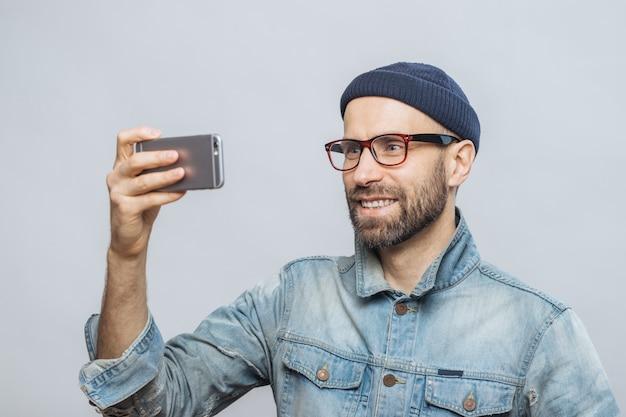Erfreuter lächelnder bärtiger mann mit glücklichem ausdruck wirft an der kamera des intelligenten telefons auf