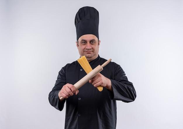 Erfreuter männlicher koch mittleren alters in kochuniform-kreuzungsmesser und spaghetti in seiner hand auf isolierter weißer wand