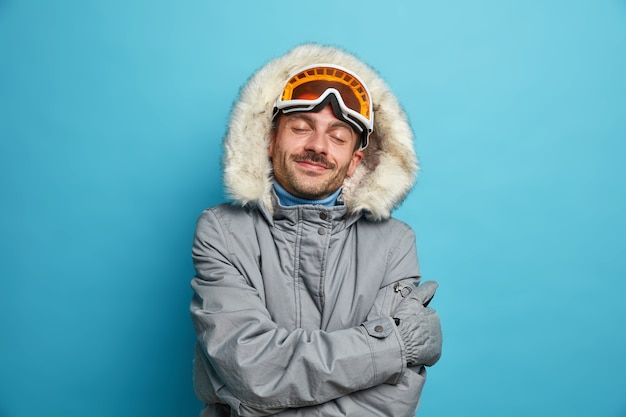 Erfreuter männlicher snowboarder fühlt sich wohl und warm in der winterjacke umarmt sich und erinnert sich an einen schönen moment des skifahrens an schönen kalten tagesständen mit geschlossenen augen.