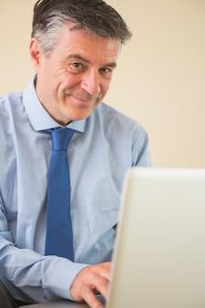 Erfreuter mann, der einen laptop sitzt auf bett verwendet