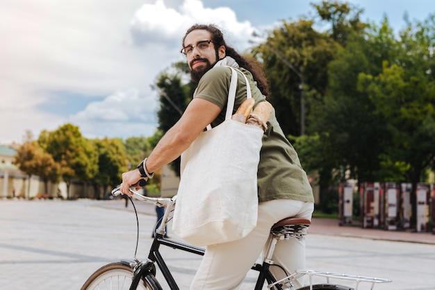 Erfreuter netter mann, der eine tasche hält, während er vom supermarkt reitet
