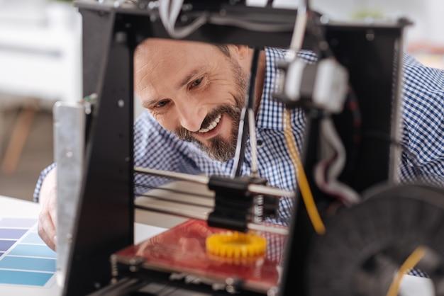 Erfreuter positiver netter mann, der das 3d-modell betrachtet und lächelt, während er sich über das ergebnis seiner arbeit freut