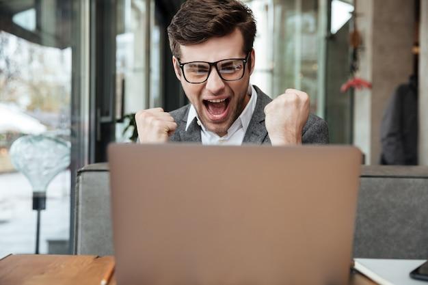 Erfreuter schreiender geschäftsmann in den brillen, die durch die tabelle im café sitzen und freuen sich beim betrachten der laptop-computers