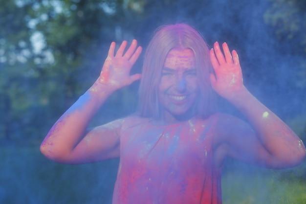 Erfreutes blondes mädchen, das beim sommer-holi-festival in einer wolke aus blauer farbe posiert