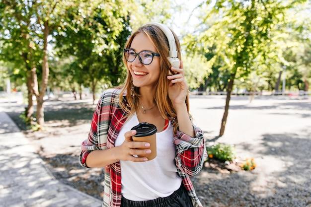 Erfreutes blondes mädchen in brille, das in weißen kopfhörern aufwirft. porträt der entzückenden jungen frau, die auf natur mit tee steht.