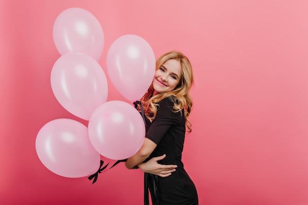 Erfreutes blondes mädchen mit glücklichem lächeln, das mit großen luftballons steht. frohe lockige kaukasische dame, die auf geburtstagsfeier wartet.