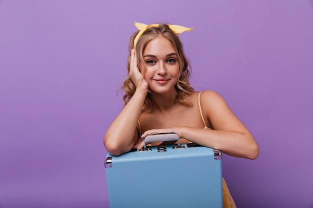 Erfreutes dunkeläugiges mädchen, das mit blauem koffer posiert. begeisterte süße dame, die auf veilchen mit sanftem lächeln sitzt.